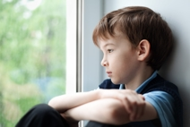 A young boy sitting by and looking out of a window